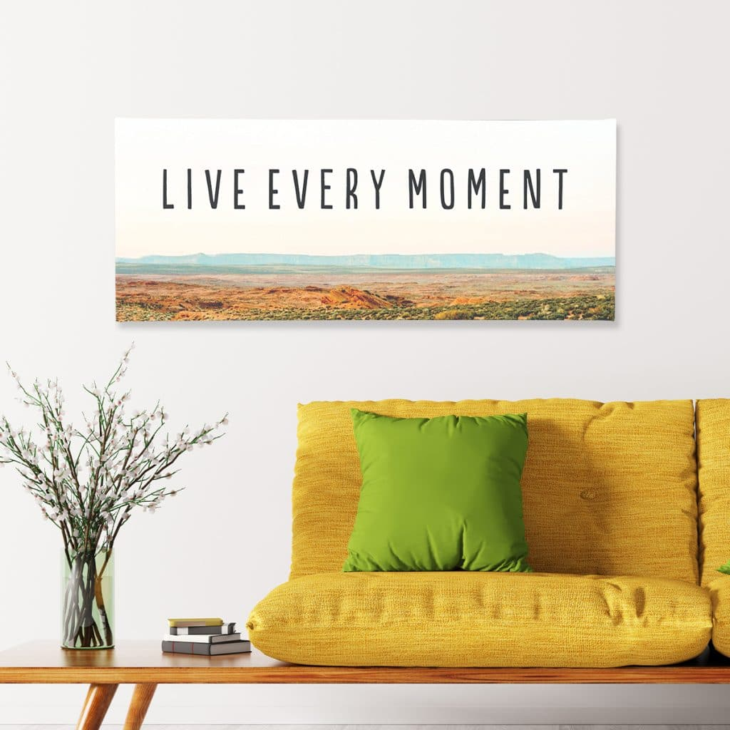 """Panoramic canvas print that reads """"Live every moment"""" hanging over a yellow couch"""