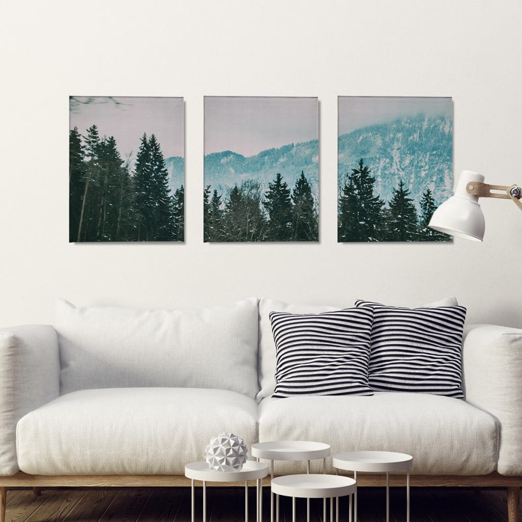 Split canvas prints of a mountain scene hanging over a white couch