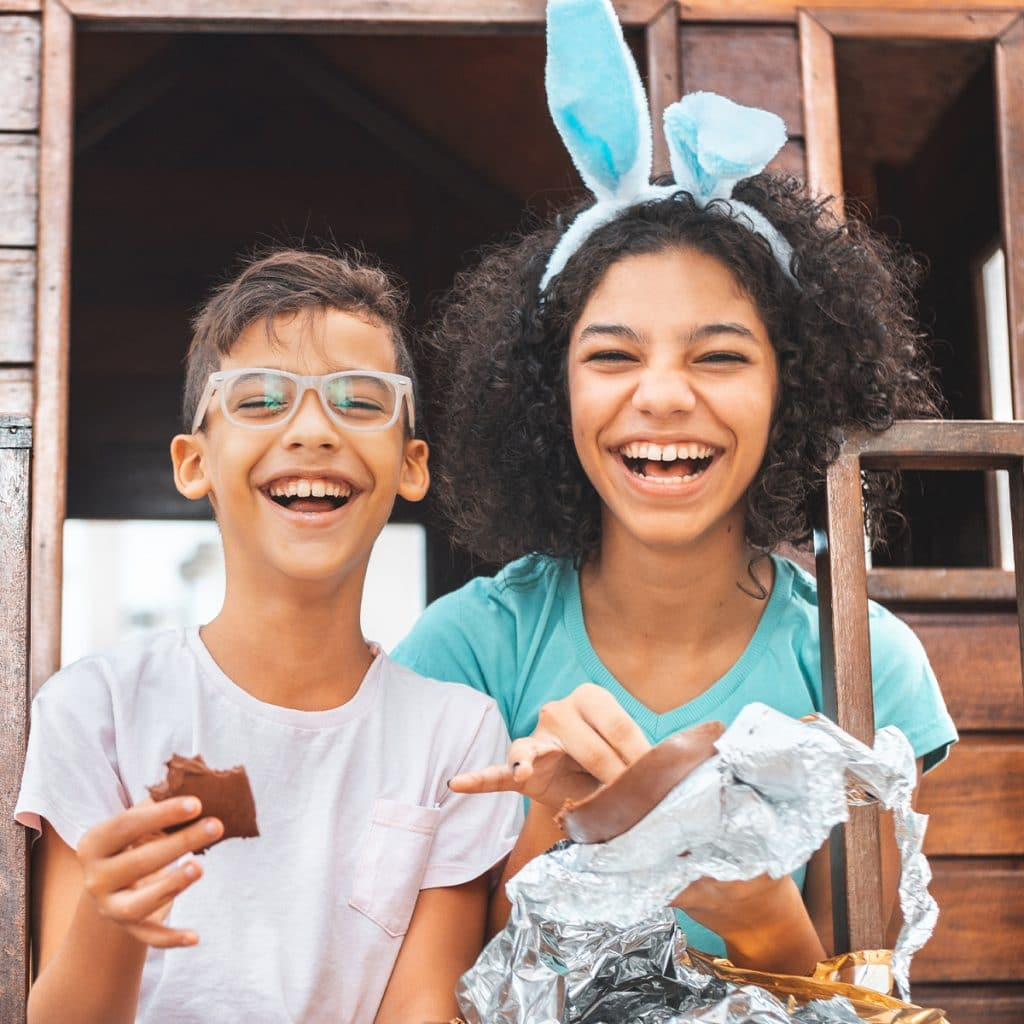 Two kids laughing and smiling while eating chocolate and wearing Easter bunny ears