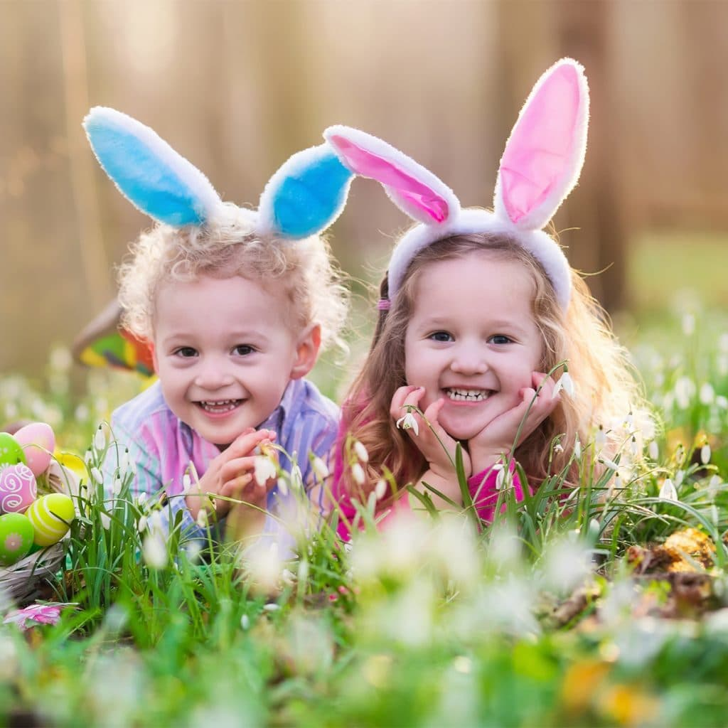 Two toddlers laying in the grass, surrounded by easter eggs, wearing pink and blue bunny ears.