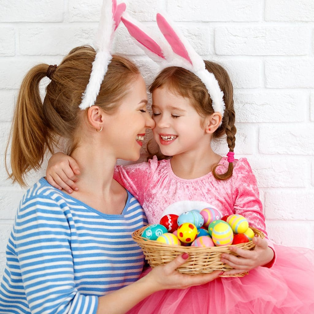 Mom and daughter smiling, wearing bunny ears, and holding a basket of Easter eggs