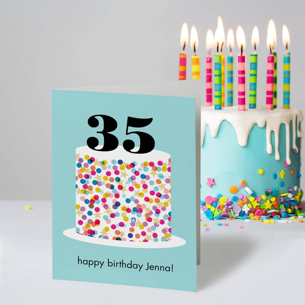 Sprinkle Cake birthday greeting card standing next to a beautiful blue sprinkled cake with candles