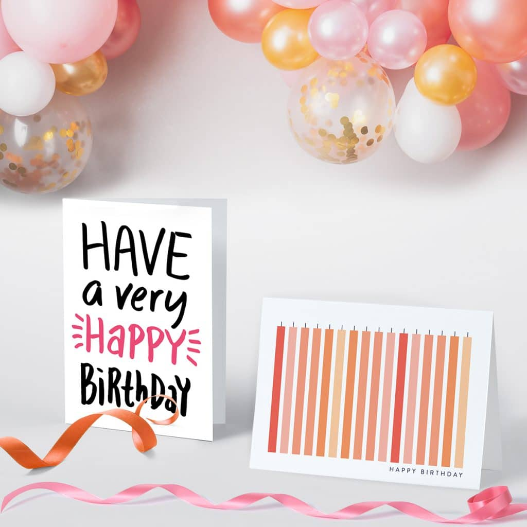 Pink birthday greeting cards standing up surrounded by bright pink ribbon