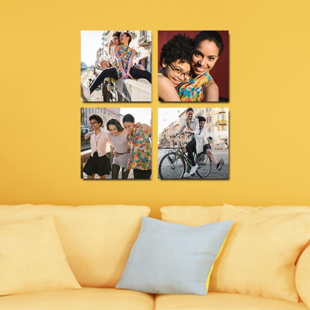 Four 8x8 photo tiles hanging on a yellow wall above a yellow couch