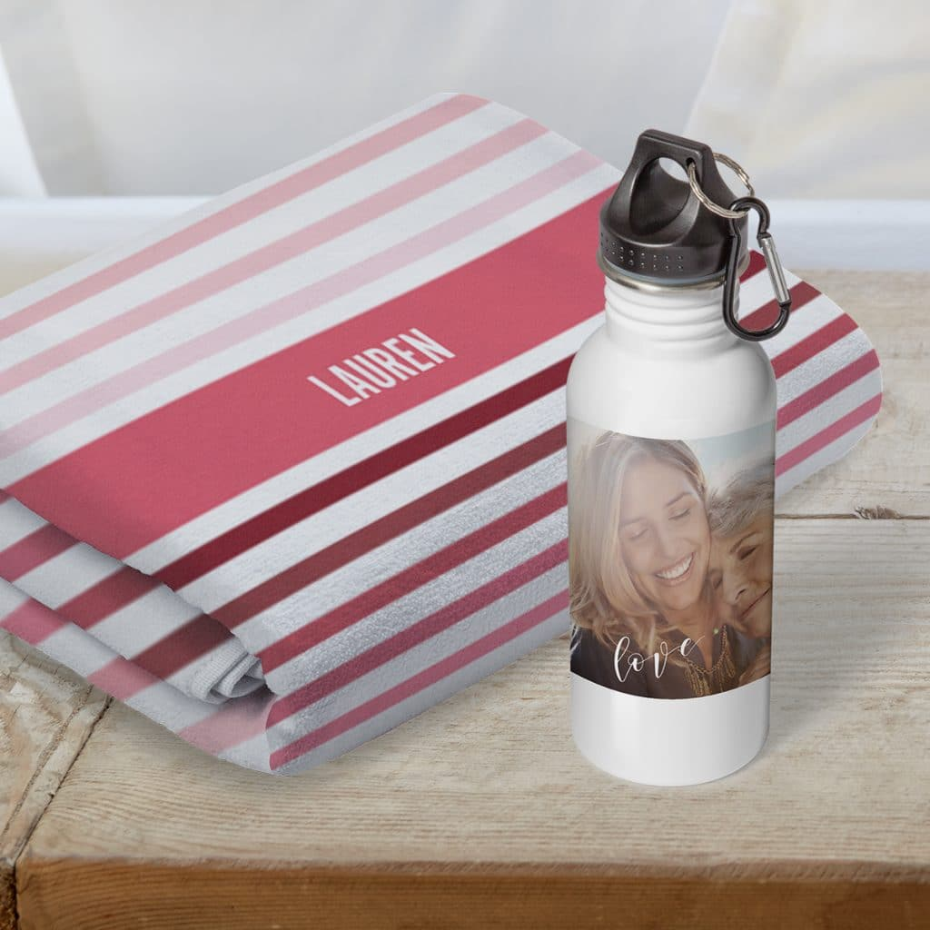 A customized beach towel with the name Lauren folded behind an insulated water bottle featuring a sweet photo of mother and grown daughter