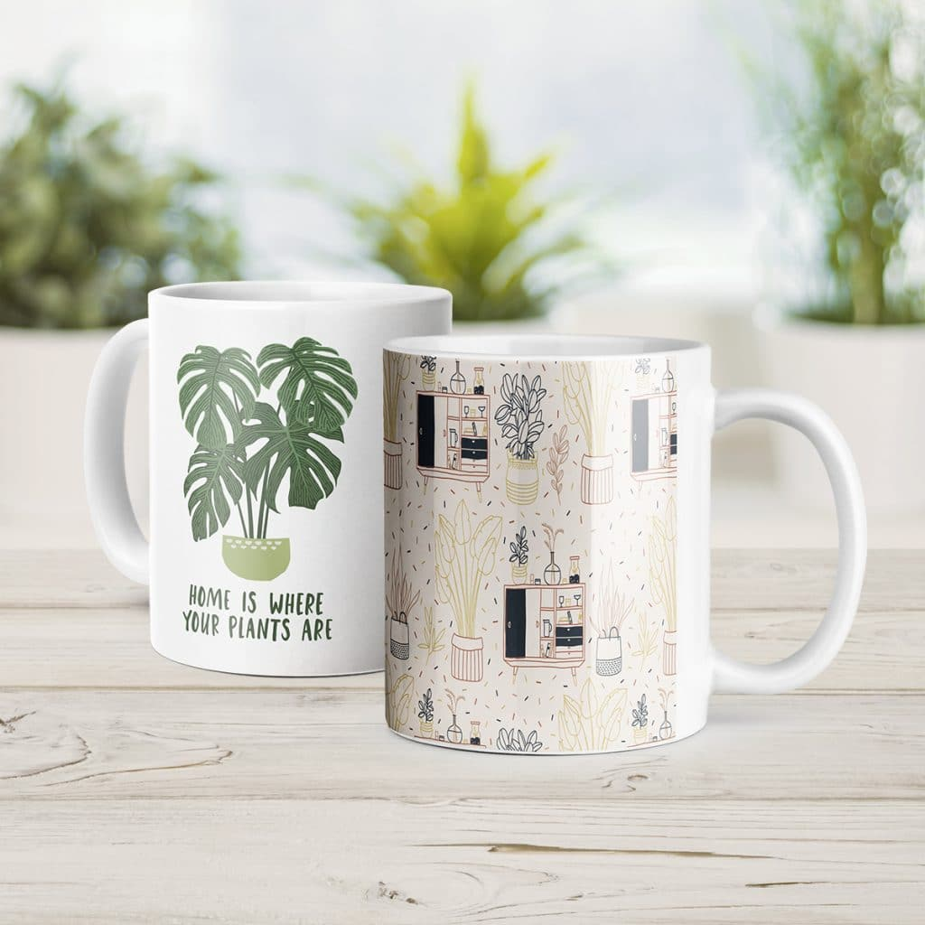 """Two white coffee mugs, one saying """"Home is where your plants are"""" with a plant illustration, the other featuring a linework style illustration of home decor and plants"""