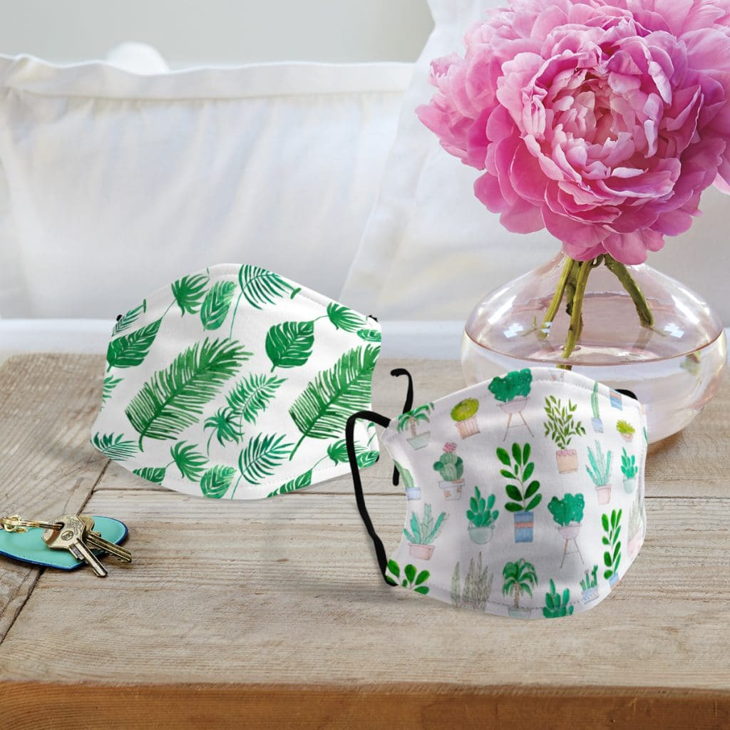 Two face masks featuring different house plant and greenery-inspired prints