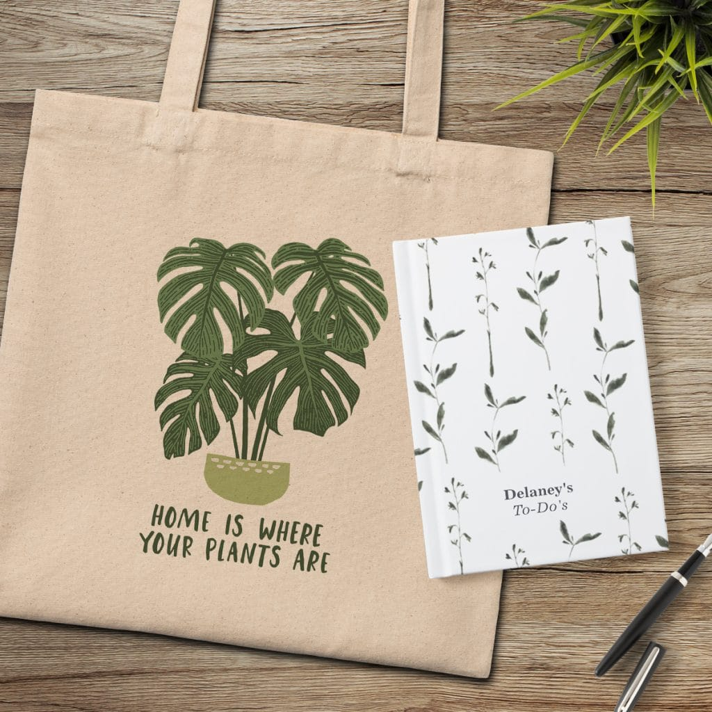 """Canvas tote bag featuring """"Home is where your plants are"""" design laying with a hardcover notebook featuring a leafy greenery design"""