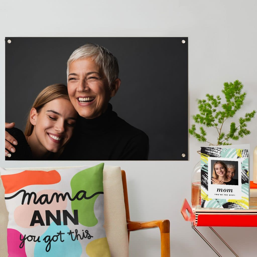Acrylic print photo of mom and daughter hanging on the wall behind a custom Mom pillow and card