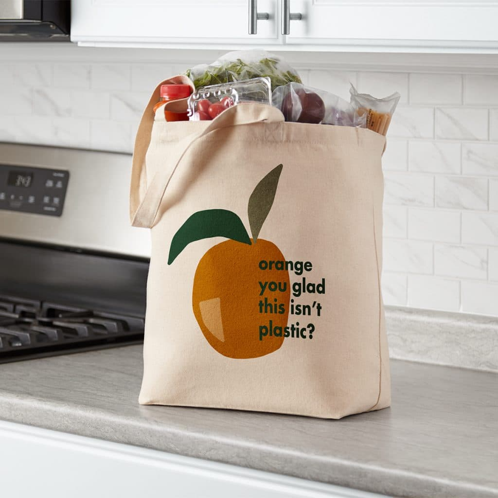 """Everyday canvas tote bag full of groceries, featuring an """"Orange you glad this isn't plastic?"""" design."""