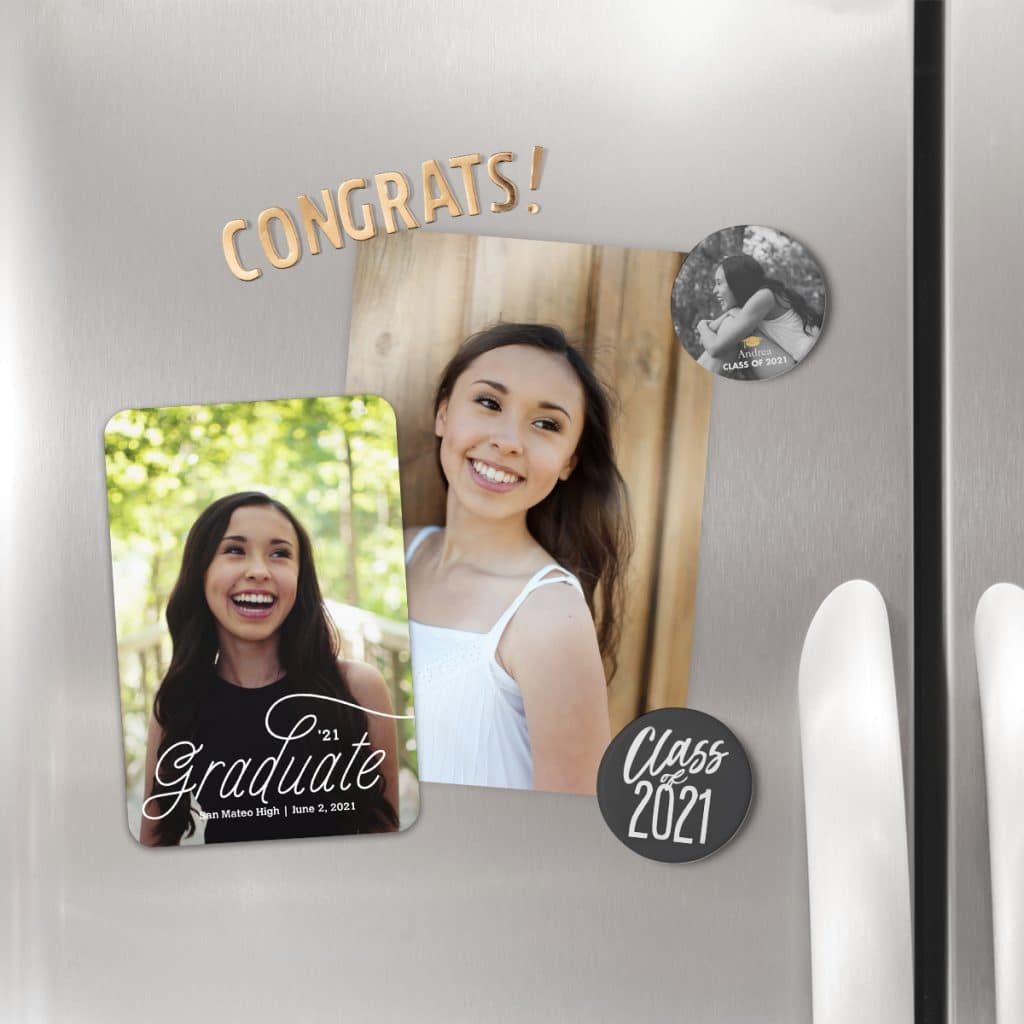 Round refrigerator magnets holding up 2021 graduation announcements