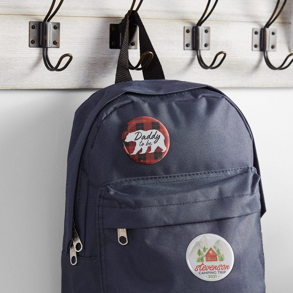 """Daddy-to-be and """"Camping Trip"""" pins shown on a navy blue backpack hanging from a hook"""