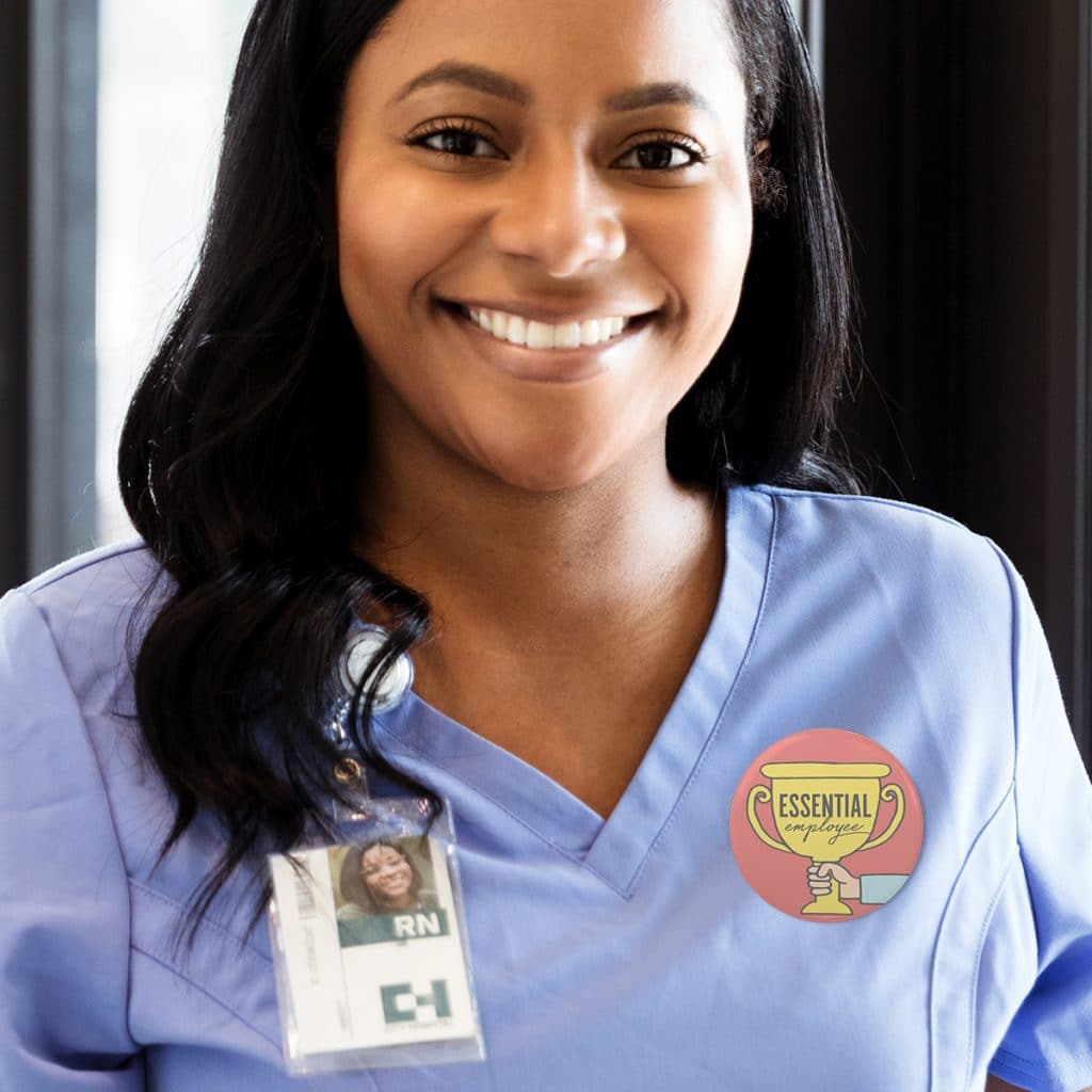 """Photo of a nurse wearing an """"Essential Employee"""" button pin"""