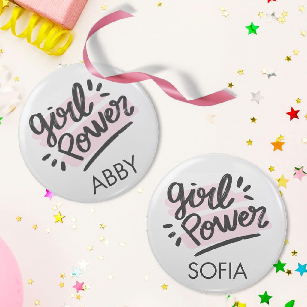 """Two """"Girl Power"""" button pin designs with the names Sofia and Abby laying on a table surrounded by star confetti"""