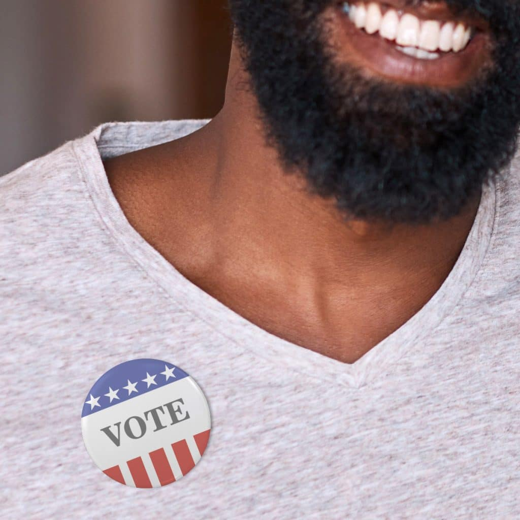 Photo of a man smiling wearing a VOTE pin