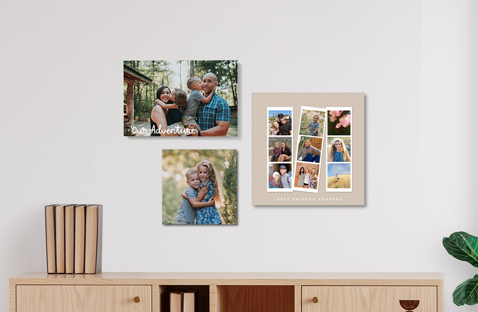 Three photo tiles in three different sizes hanging on a wall over a credenza