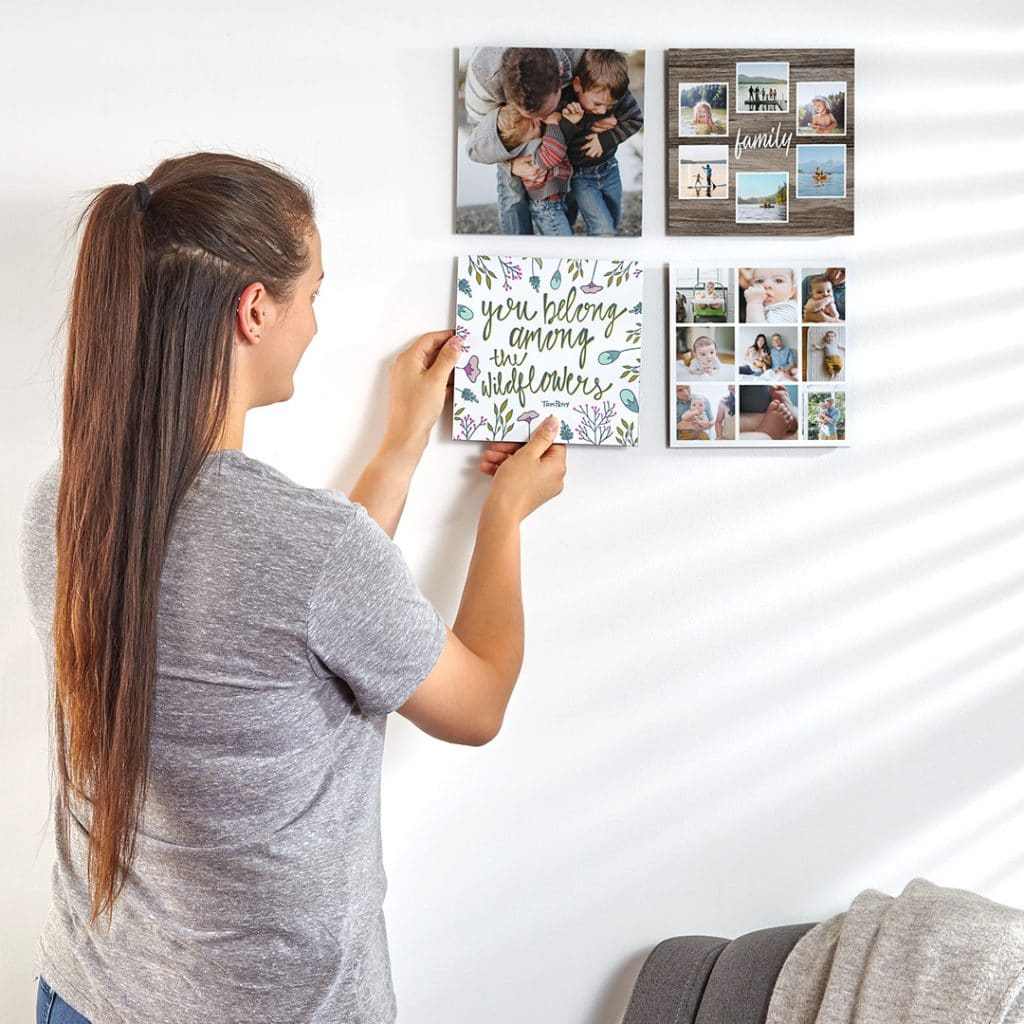 Woman hanging photo tiles on a wall