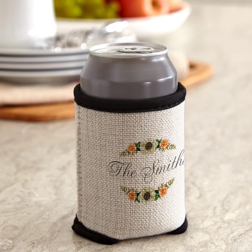 Floral Frame cloth can cooler holding a can, sitting on a kitchen counter