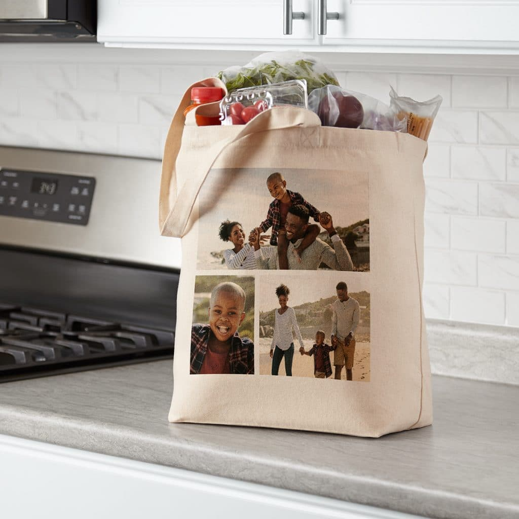 Image of a canvas tote bag sitting on a kitchen counter. The tote is decorated with a collage of family portraits, including mom, dad, and young son.
