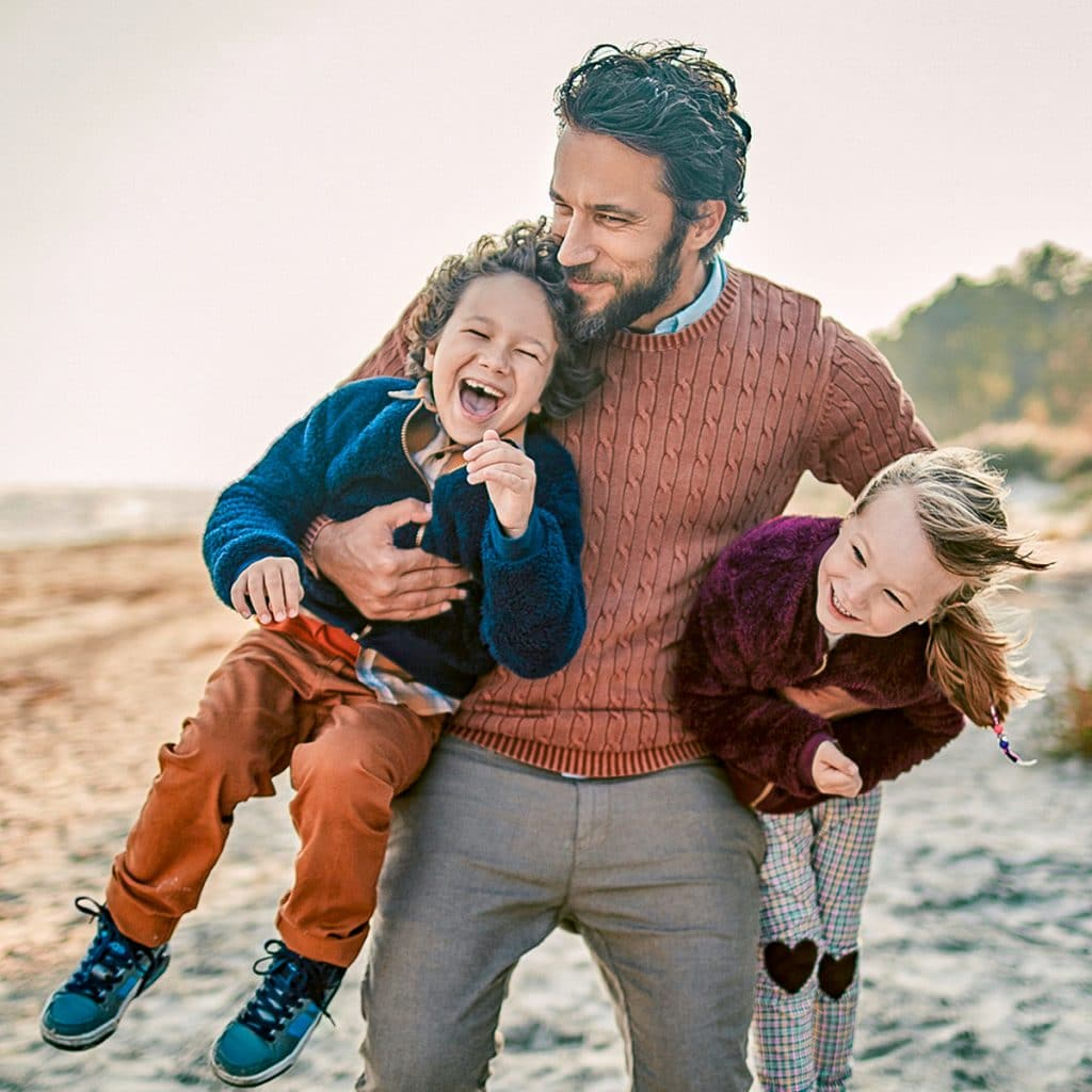 Sweet family photo of dad holding his son and daughter, laughing, on the beach
