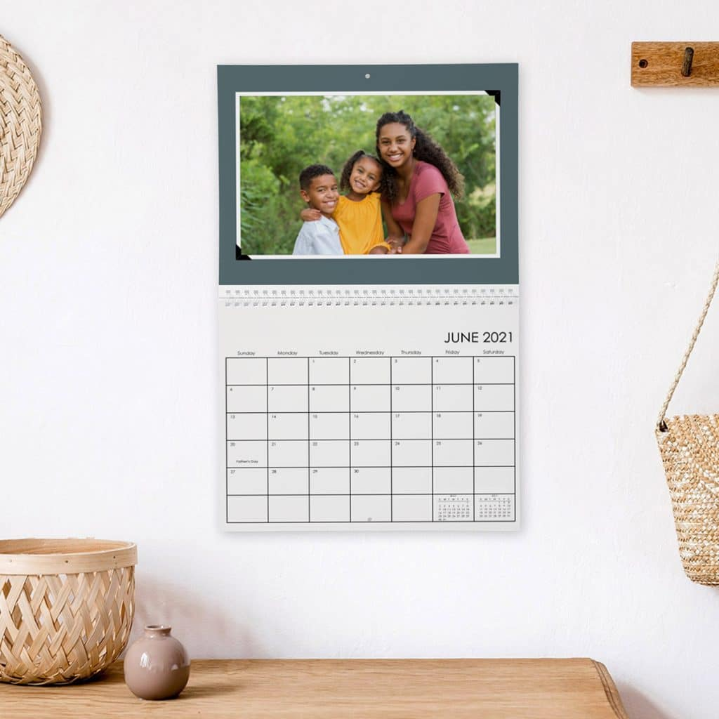 Image of a photo wall calendar hanging on a wall over a desk
