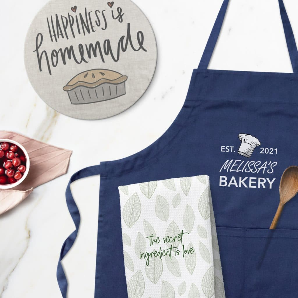 Flat lay image of kitchen accessories including a tea towel, navy blue apron, and trivet