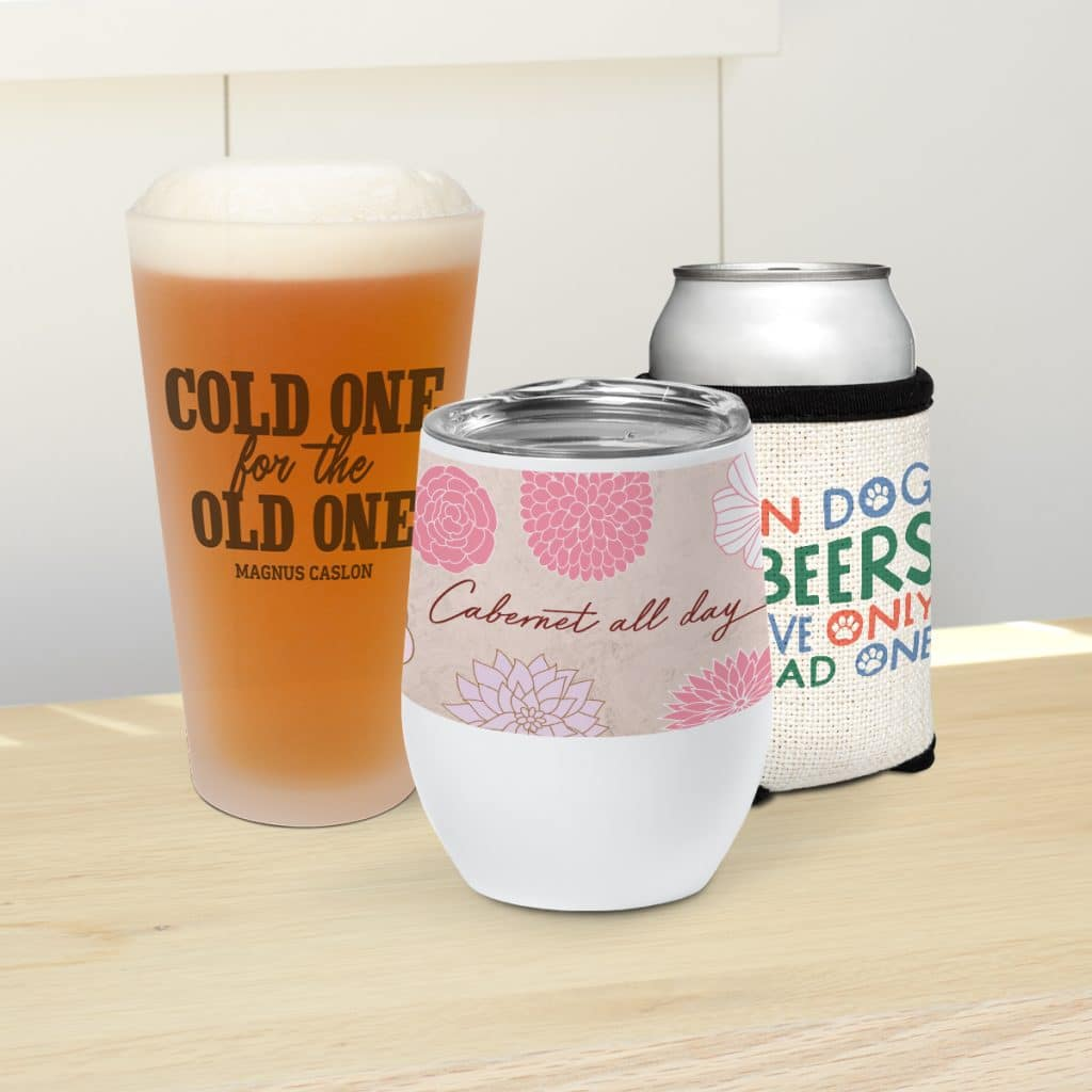 Image showcasing a drinkware collection, including a pint glass, insulated wine tumbler, and can with cloth can cooler