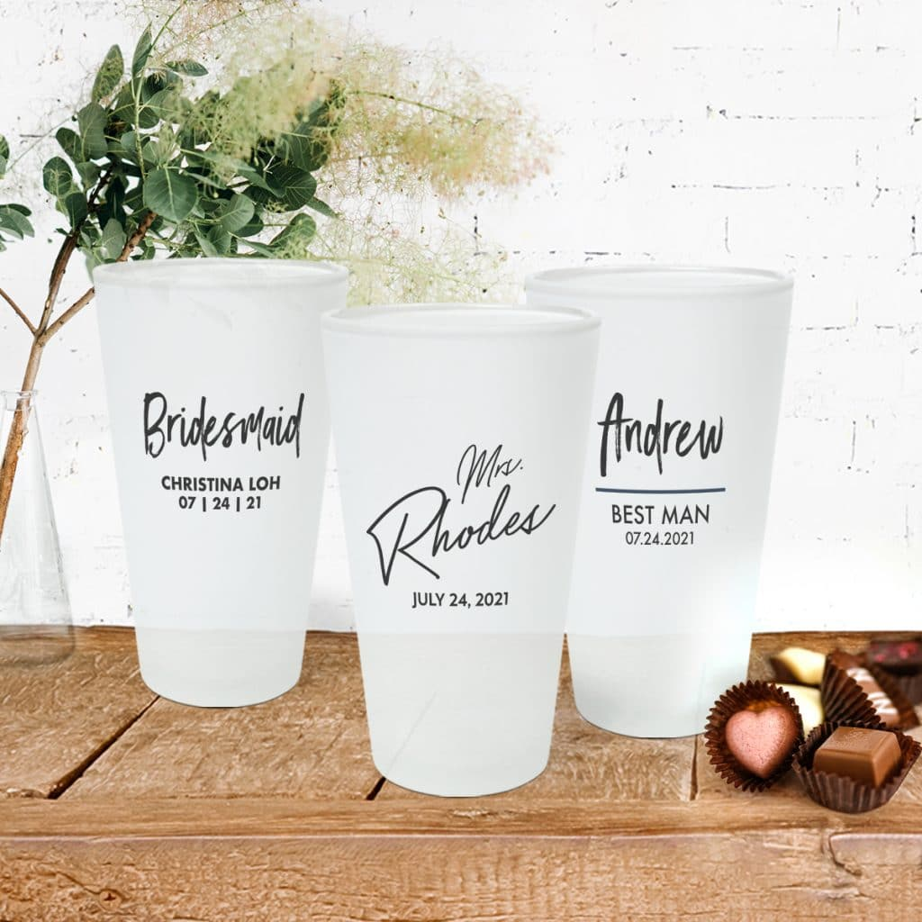 3 frosted pint glasses sitting on a table. Each pint glass features a different wedding-centric design.