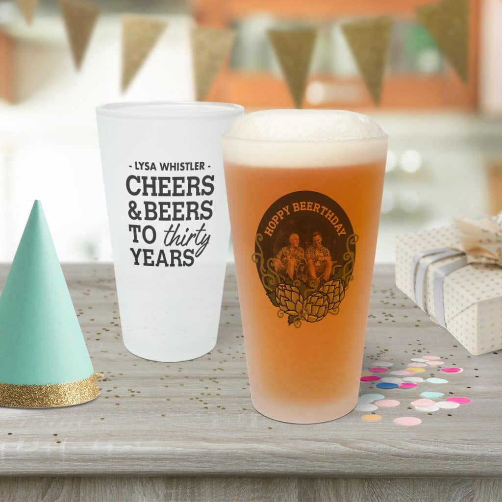 Two frosted pint glasses sitting on a table; they are part of a birthday celebration