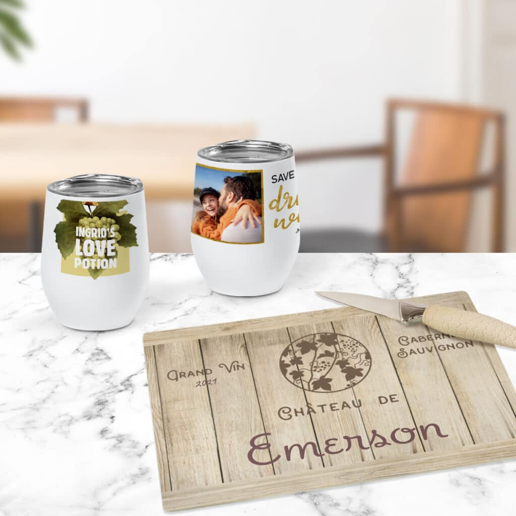 Image of two wine tumblers sitting on a countertop, each featuring wine-centric designs. In front of them is a glass cutting board featuring a wine barrel design