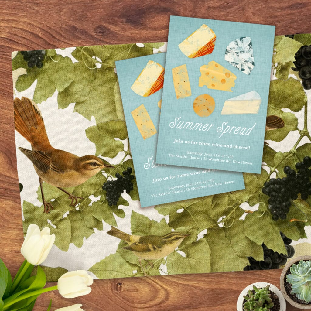 Flat lay image featuring cloth placemat with vineyard-inspired design. On top of the placemat is invitations for a wine and cheese party.