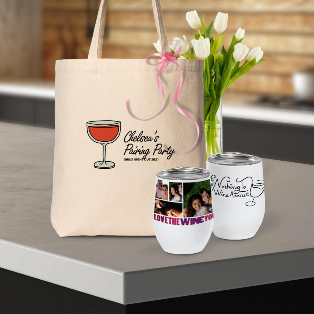 """Image of a canvas tote bag with """"Chelsea's Pairing Party"""" design sitting on a countertop. In front of the bag are two insulated wine tumblers, both featuring wine-centric designs."""